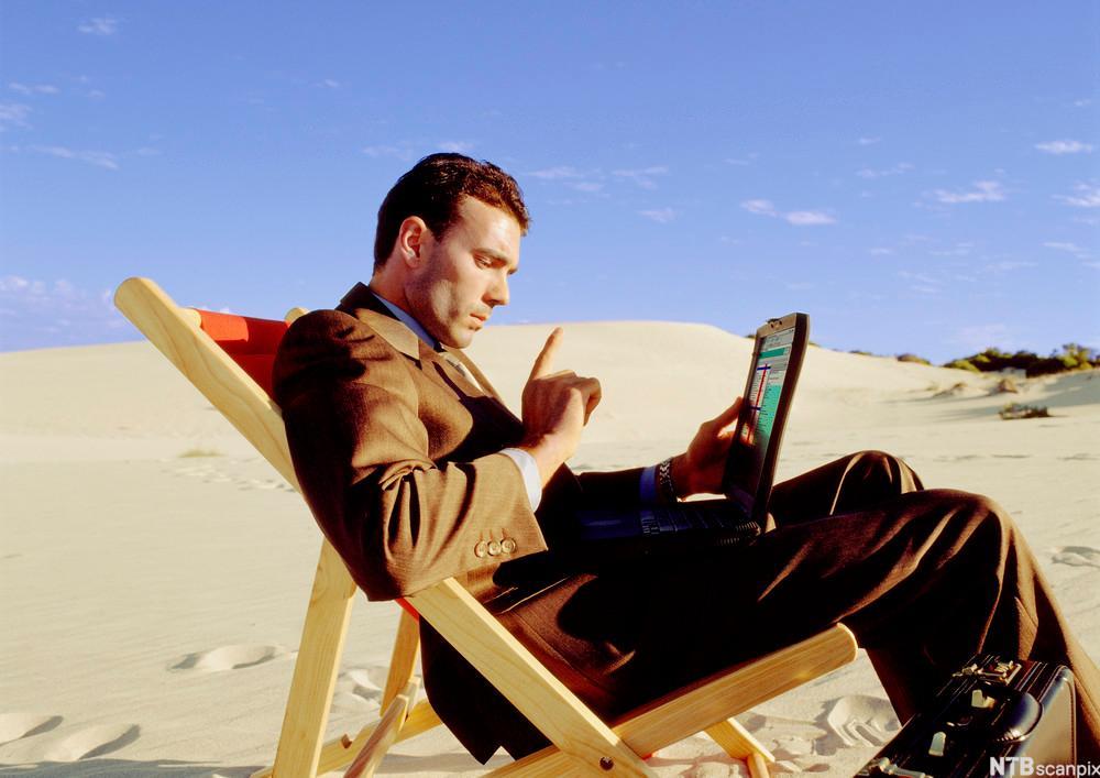 Mann sitter i en solstol med laptop i fanget ute i en ørken. Foto.