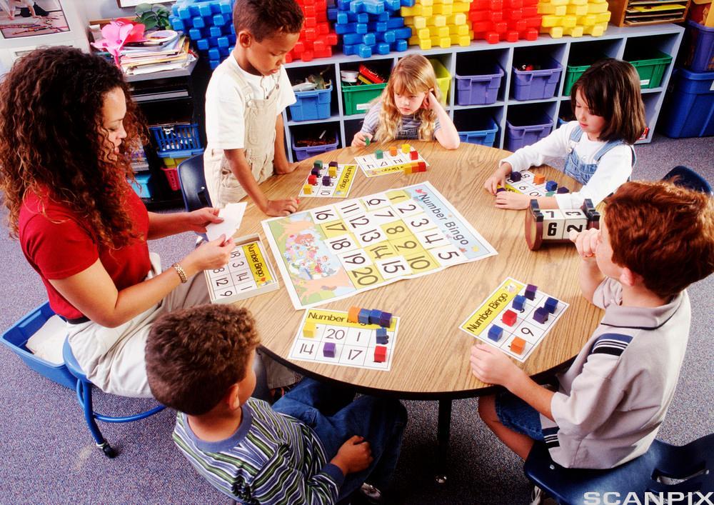 bildet viser barn som sitter å jobber med et spill - i gruppe