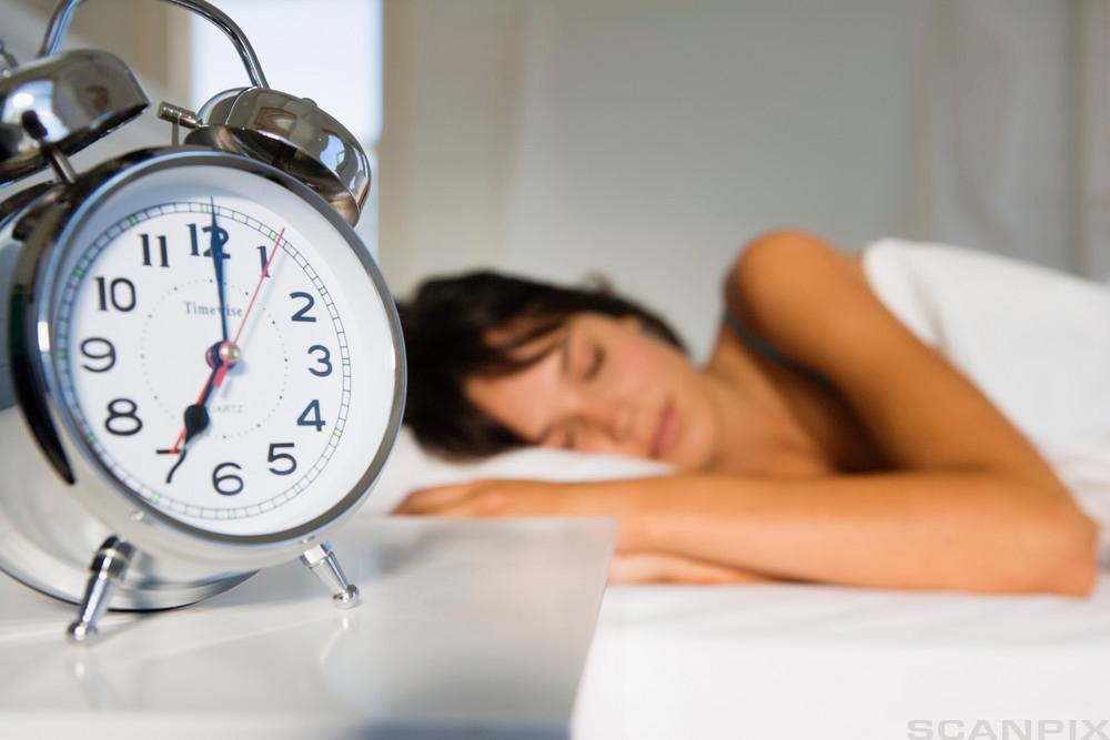 jente ligger og sover, vekkerklokke på nattbordet