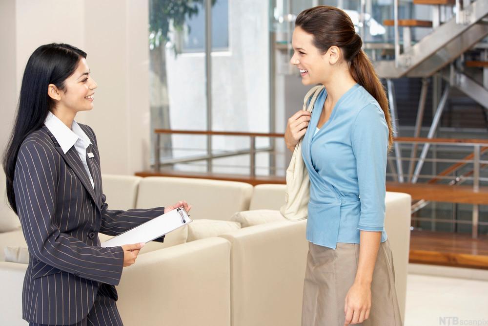 To kvinner snakker sammen i en resepsjon. Foto.