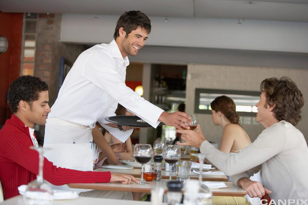 Kelner serverer drikke til gjester. Foto.