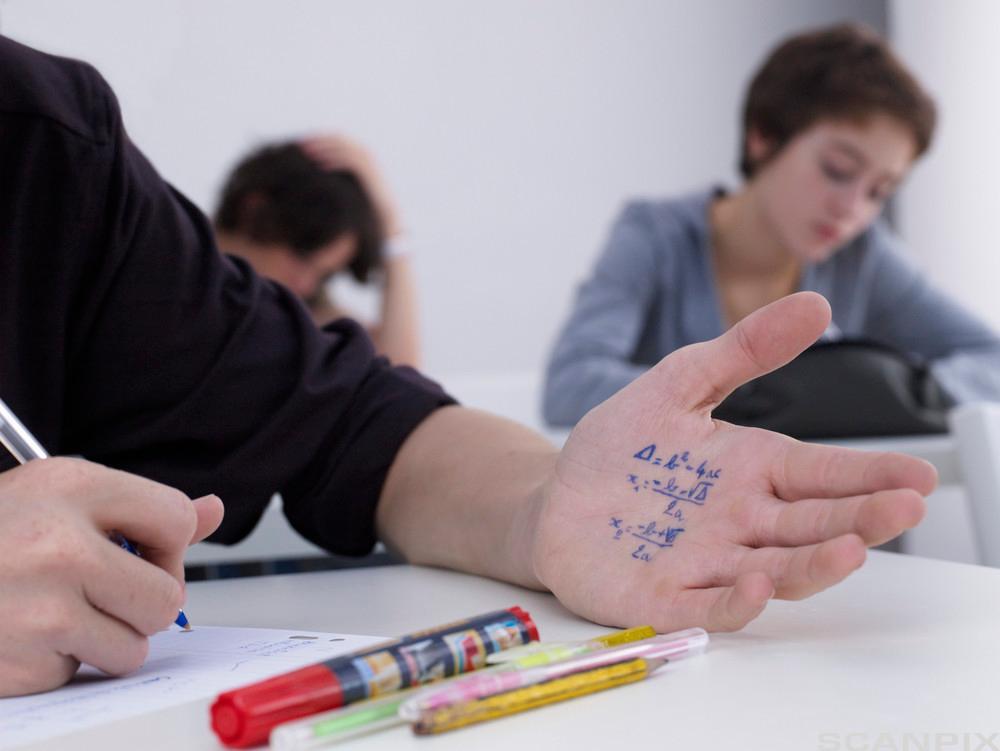 Ein gut juksar på matteeksamen ved å sjå på ein tekst skriven inne i handa. Foto.