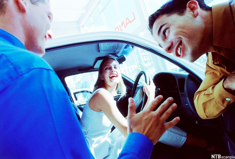 Bilde av en bilselger som selger bil til et ungt par der kvinnen sitter inne i bilen