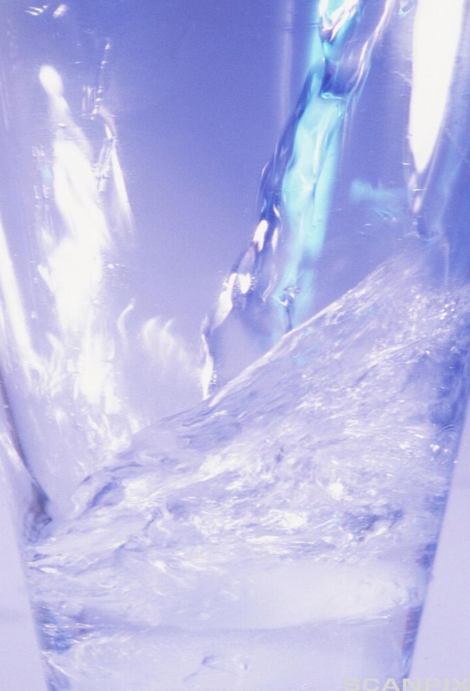 Bilete av vatn som blir helt i eit glas. Foto