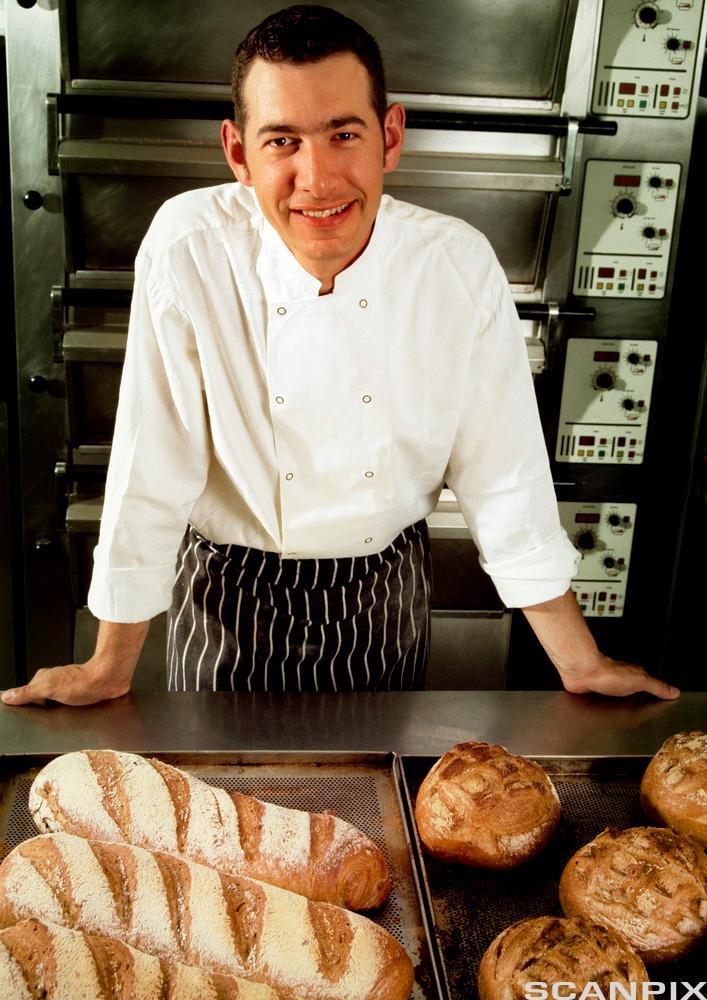 En baker viser frem nystekte brød. Foto.