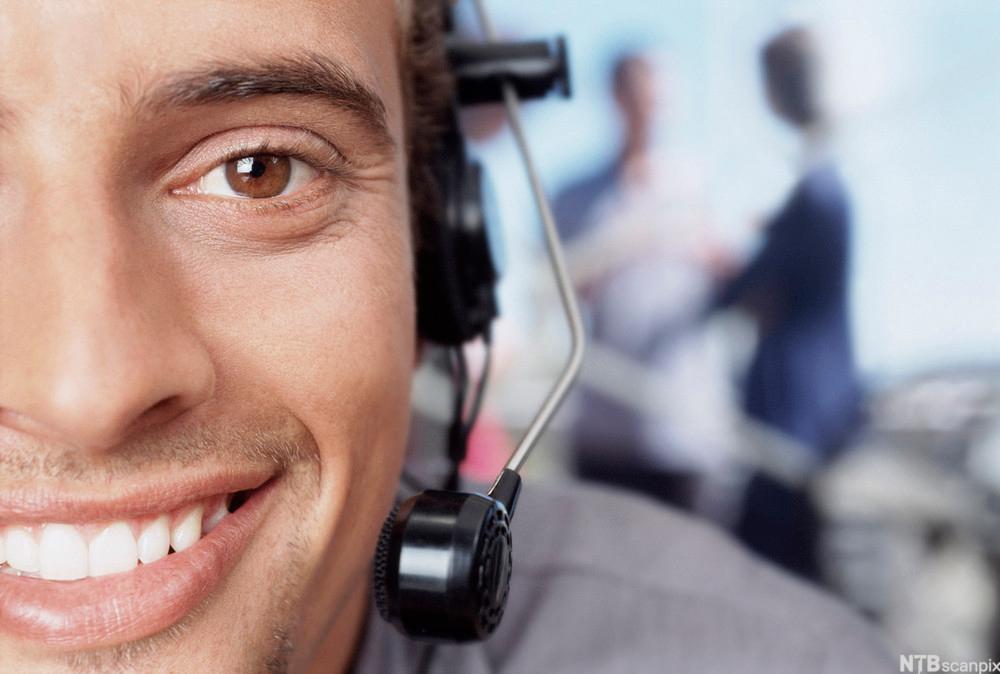 Utsnitt av ansiktet til en mann med hodemikrofon. Foto.