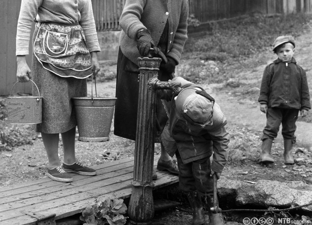 Kvinner og barn ved vannposten. Foto.