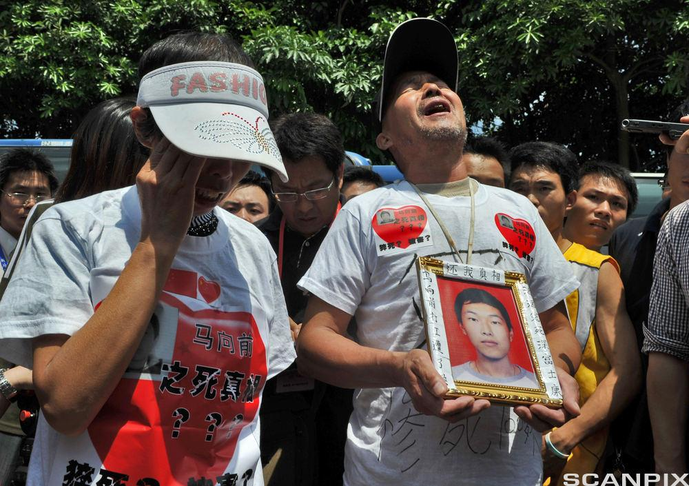 Foxconn suicides: The parents of a Foxconn employee who died last January 23, 2010 display a portrait of theur son as journalist