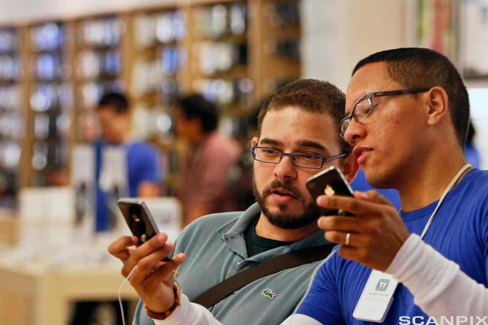 Mann lærer om de nye funksjonene til iPhone 4 mens han snakker med en ansatt i en Apple-butikk. Foto.