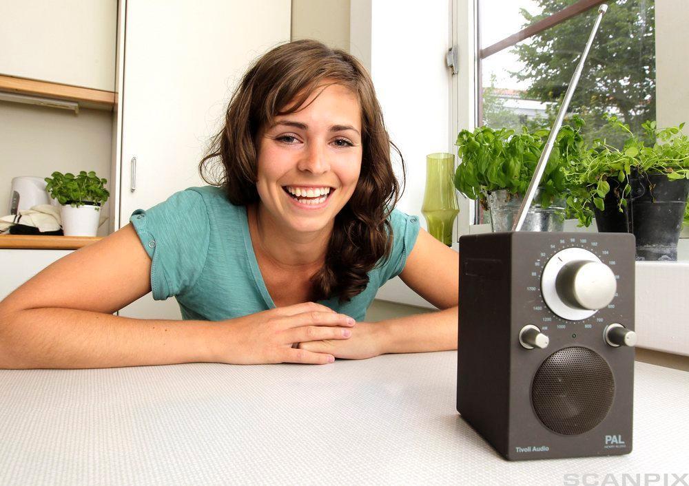 Kvinne ved kjøkkenbord mens ho lyttar til radio. Foto.