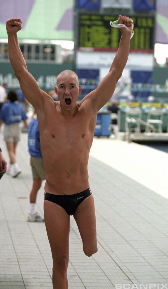 En mann løper i en svømmehall med protese. Foto.
