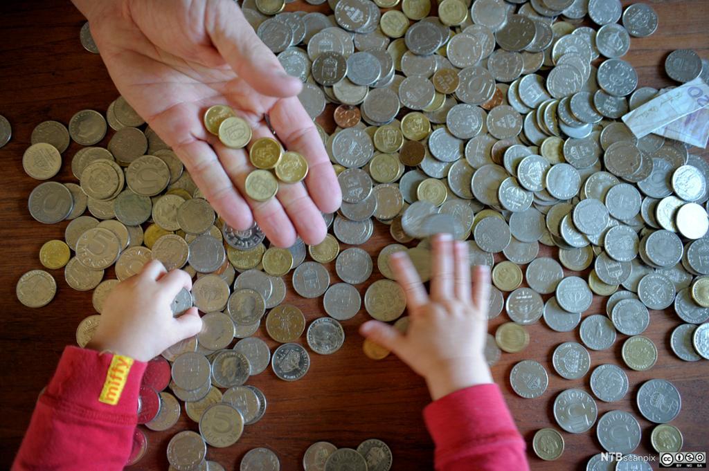 Et barn og en voksen leker med mynter på et bord. Foto.