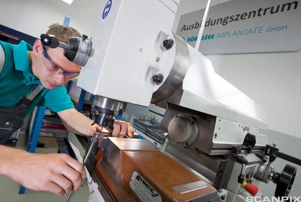 Lærling opererer fresemaskin. Foto.