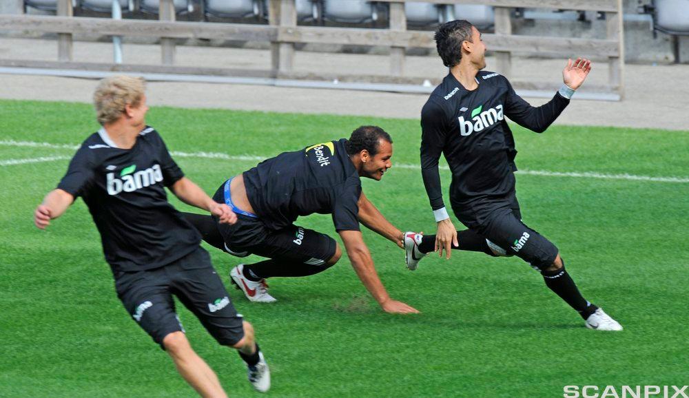 Tre personar spring på ein fotballbane. Foto.