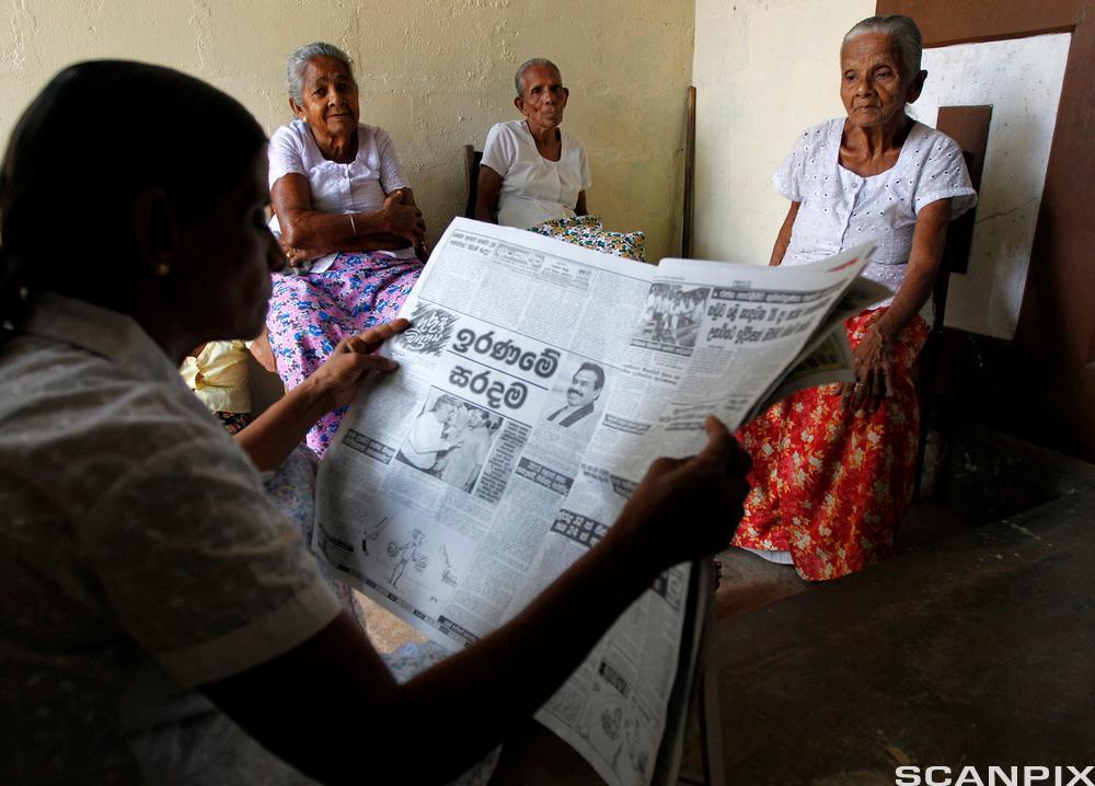 Bildet viser ein som les aviser for ei gruppe eldre personar