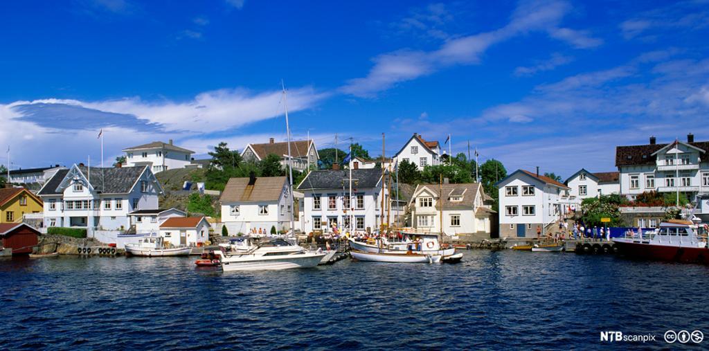 Hvite sørlandshus og båter ved kai i Lyngør i Tvedestrand. Foto.