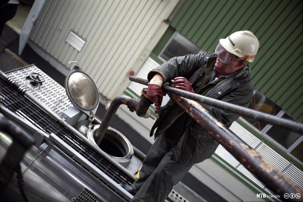 Mann fyller flytende gods på tankbil. foto.