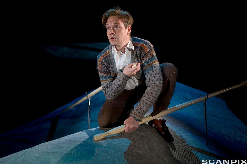 Mann sitter i båt på teaterscene. Foto.