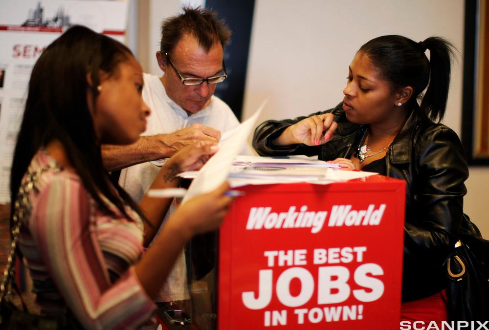 People fill out job application forms at a job fair in Los Angeles, California