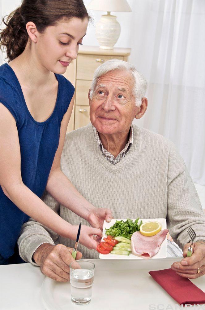 Kvinne serverer mat til en eldre mann. Foto.