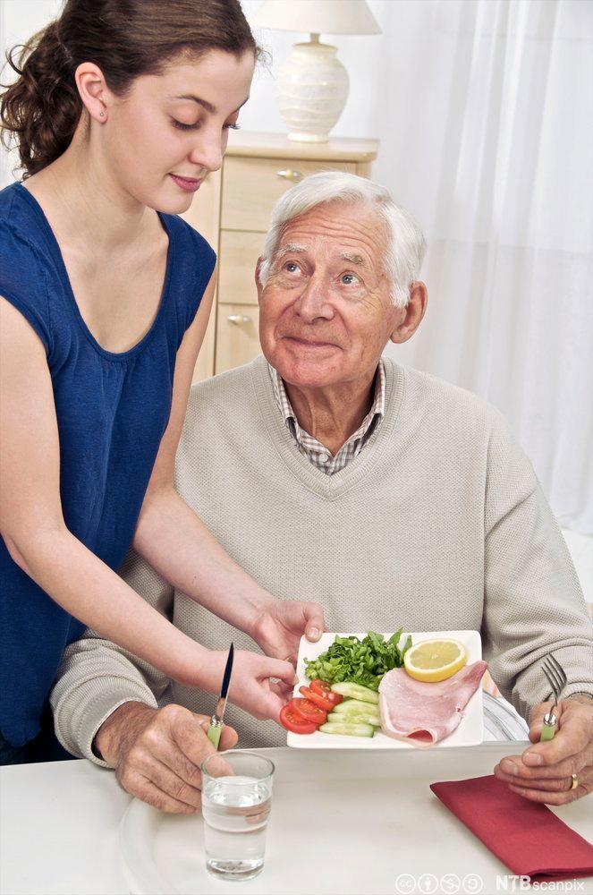 Eldre mann får servert middag. Foto.