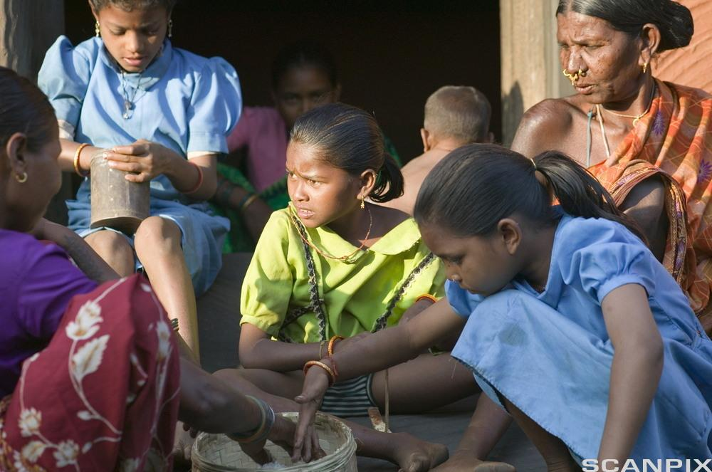 Barn som sit saman med ei dame. Foto.