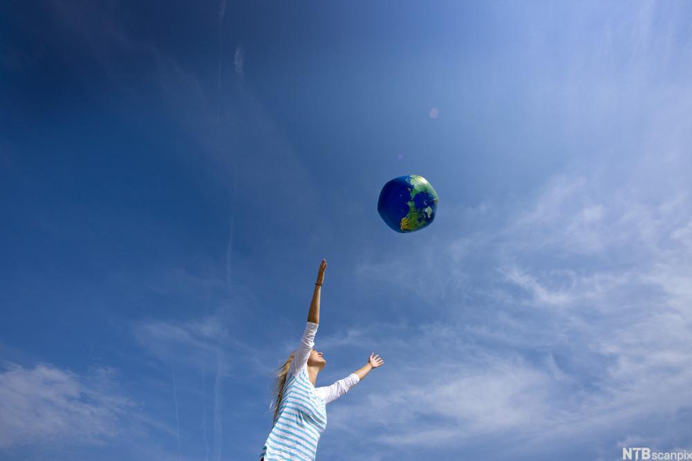 Bilde av en kvinne som kaster på en oppblåsbar ball som ser ut som jordkloden