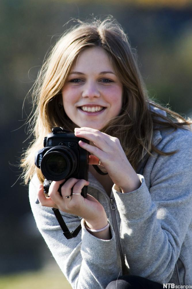 En jente holder opp fotoapparatet sitt. Foto.
