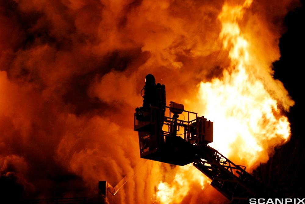 Brann i bolighus slukkes av brannmenne. Foto.