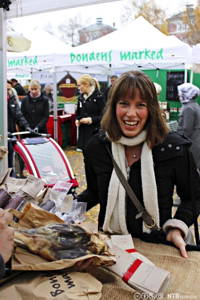 Ei dame ser på varer på Bondens marked. Foto.