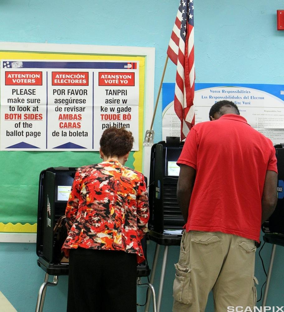 Florida Voters Head to Polls for Midterm Elections. Voters mark their ballots in polling place featuring instructions in English