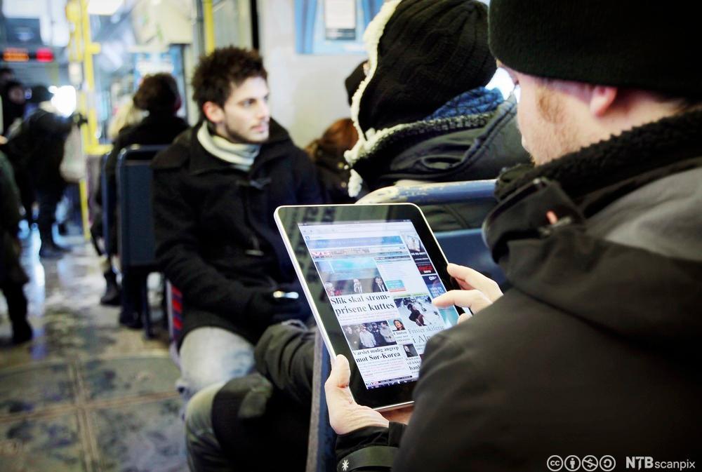 Mann leser avis på ipad på trikken. Foto.