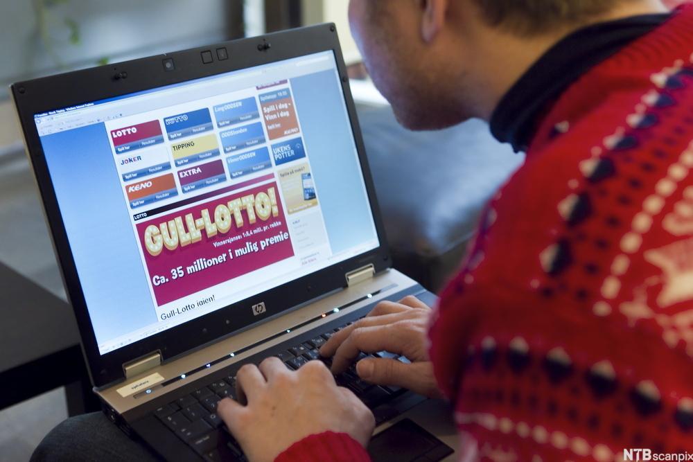 Bilde av en mann som sitter foran en laptop og ser på hjemmesiden til Norsk Tipping.