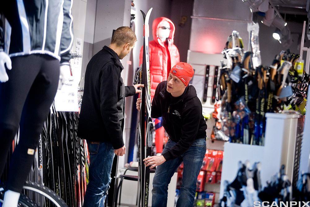To menn som ser på ski i en sportsbutikk. Foto.