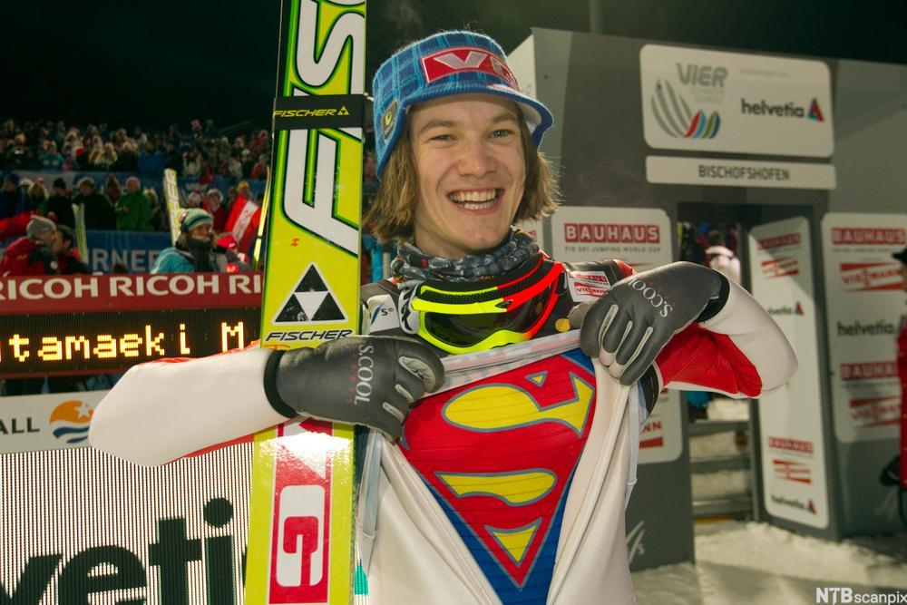 Skihopper Tom Hilde viser at han har Supermann-trøye under hoppdressen. Hilde har nettopp vunnet et hopprenn og er strålende fornøyd.