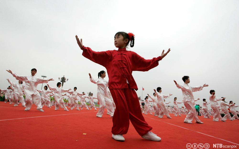 En jente utfører Tai chi på Den himmelse freds plass i Beijing. Foto.