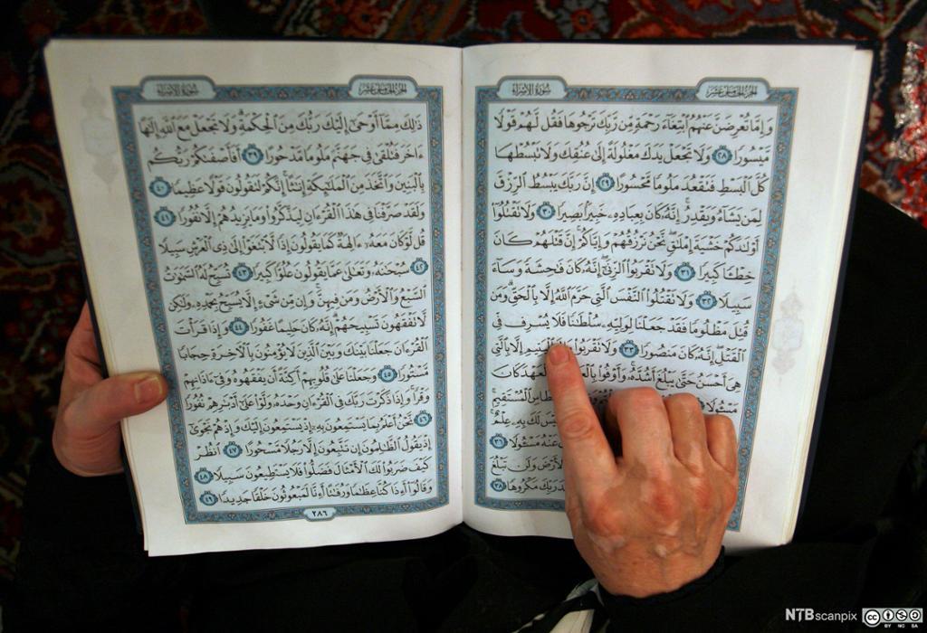 En hånd følger linjene i Koranen mens noen leser. Foto.