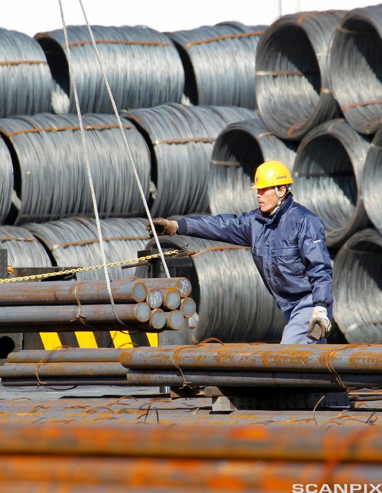 En arbeider flytter stålstenger og stålkveiler