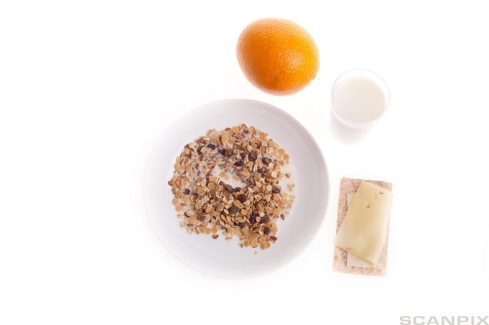 Kornblanding, knekkebrød med ost, appelsin og glass med melk. foto.