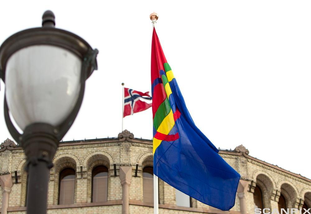 Det samiske flagget ved Stortinget. Det norske flagget henger bak .Foto.