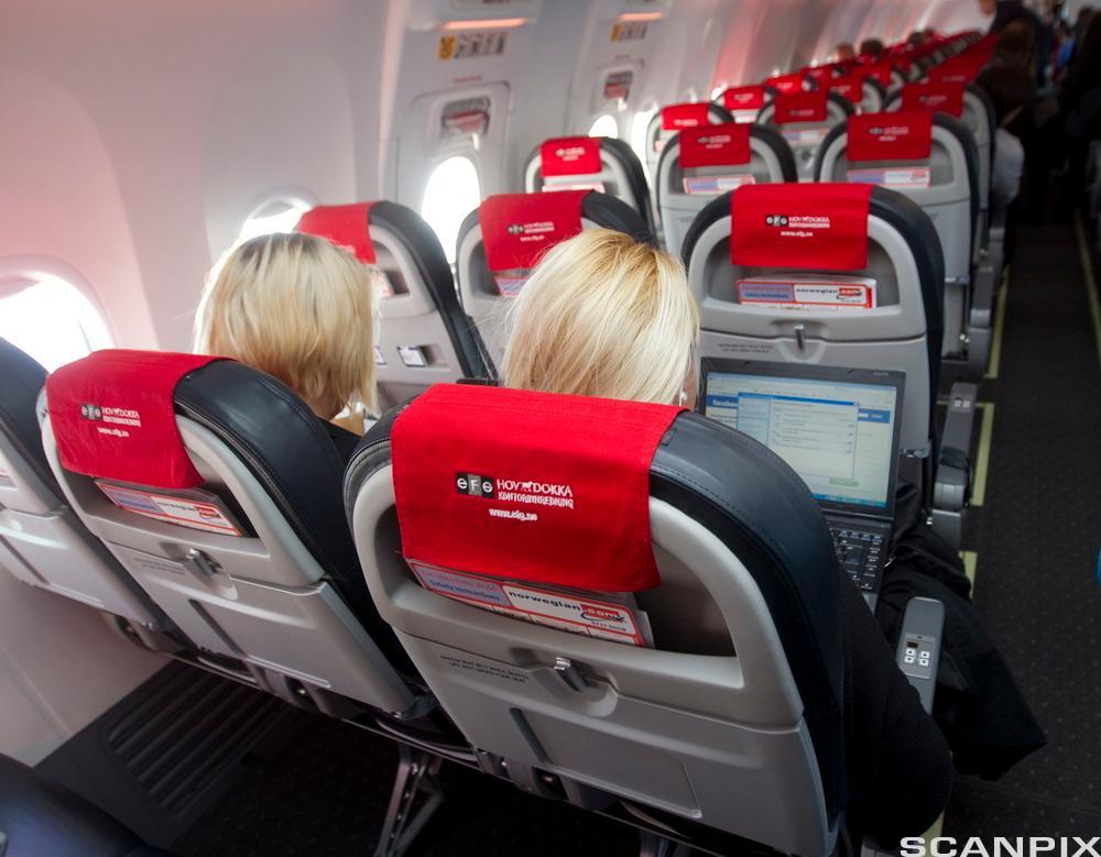 Passasjerer om bord i et Norwegian-fly. Foto.
