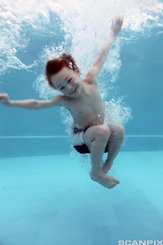 Barn svømmer under vann. Foto.