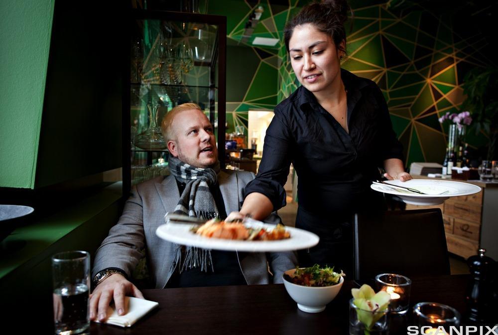 Servitør serverer en gjest . Foto