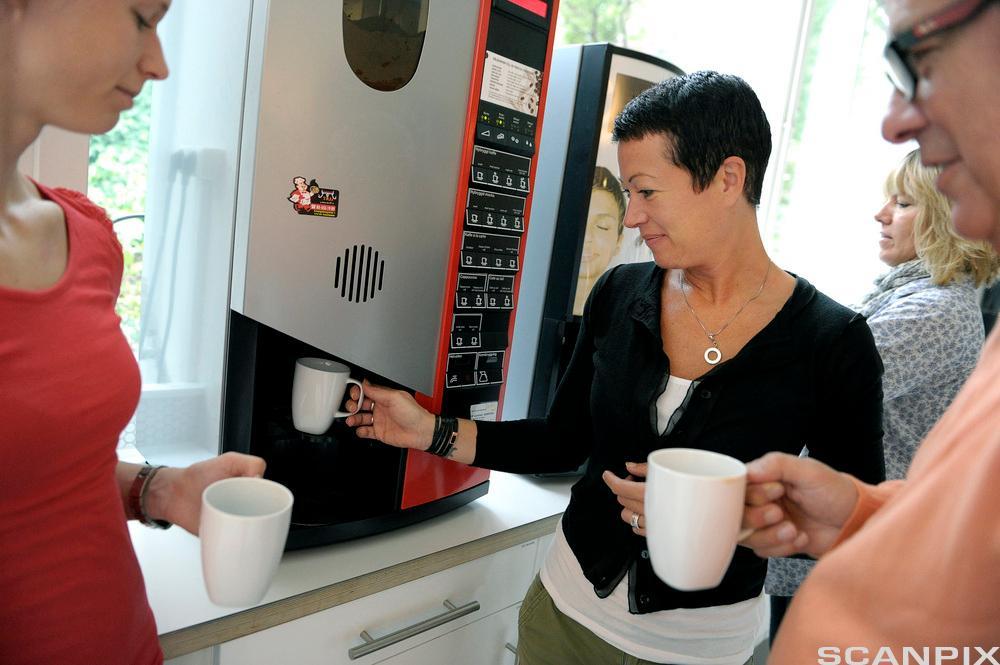 Kollegaer står rundt en faffemaskin på kontoret. Foto.