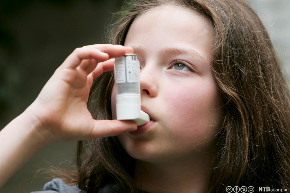 Jente som tar astmamedisin. Foto.