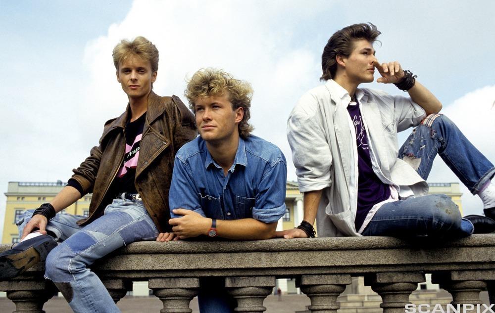 De tre medlemmene i popgruppa Aha med slottet som bakgrunn. Foto.