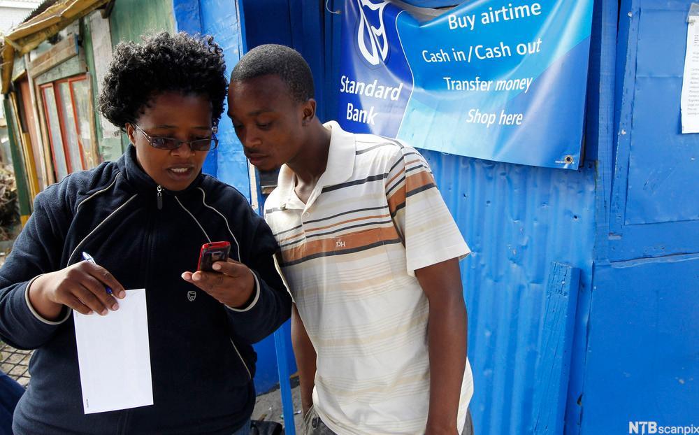 kvinner viser hvordan man bruker banktjenesten på mobiltelefon