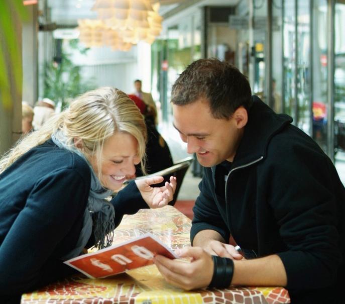 Bilde av mann og kvinne som sitter på en restaurant og studerer en meny
