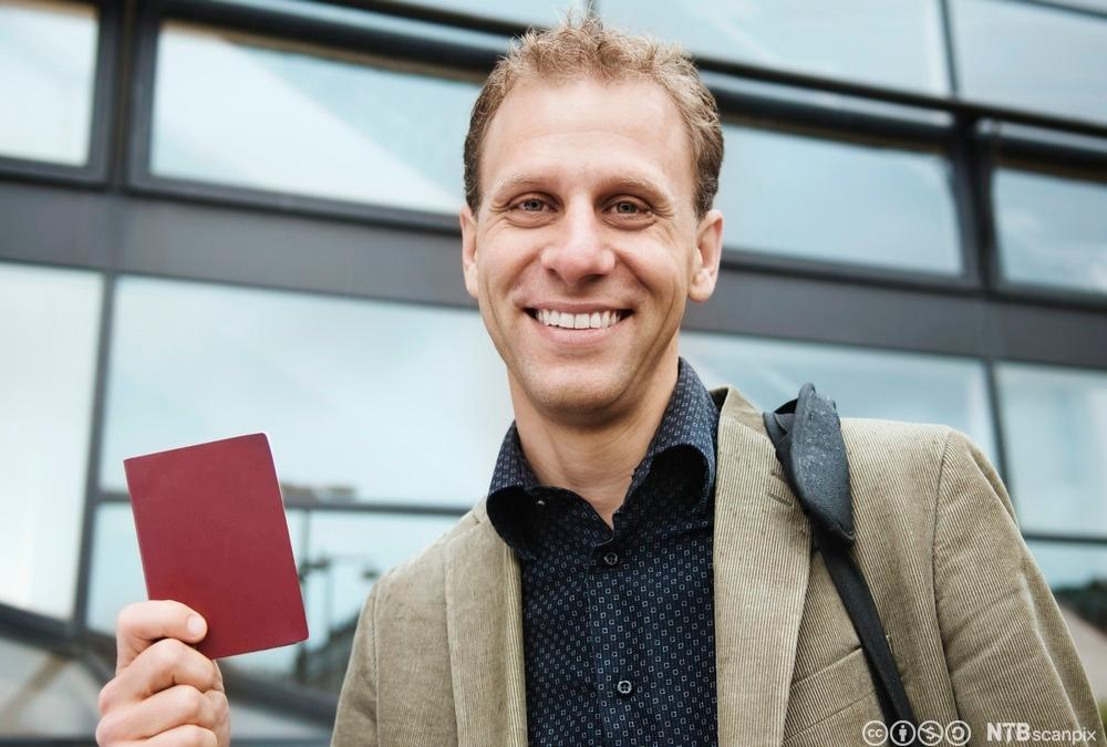 Mann med et pass i hånda. Foto.