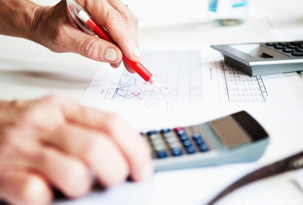 Hender til en som jobber med penn, papir og kalkulator. Foto.